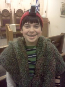 Max is wearing Tefillin (phylacteries) and a self-made Tallit (prayer shawl) for morning services.